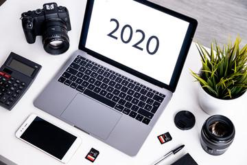 Espacio de trabajo con cámara, portátil , calculadora y smartphone de un fotógrafo profesional y diseñador