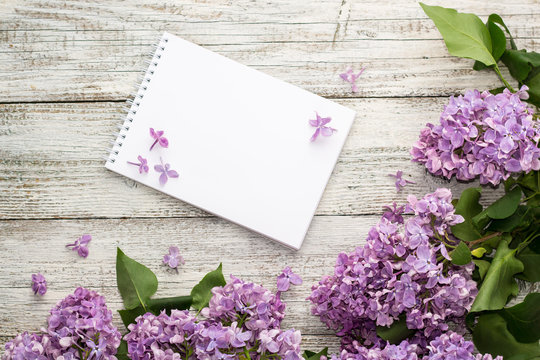 Clean notepad with spring lilac flowers on white wooden background