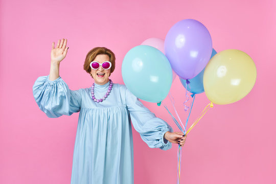 Cute old woman with balloons in blue suit disco dancer. Animator of children's parties, funny clown on a pink background