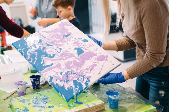 Young people are fond of drawing. Acrylic paint flows over the canvas. chaotic drawing.
