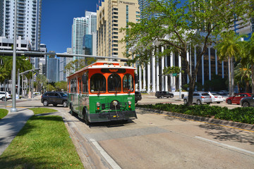 Green trolley goes on Downtown Miami street.