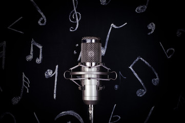 microphone on the background of the board for chalk with painted notes, concept time to record a...