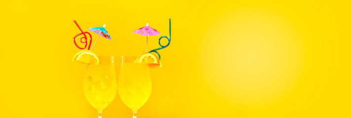two summer cocktails with straws on a yellow background, panoramic mock-up, image with space for text, concept of summer holidays