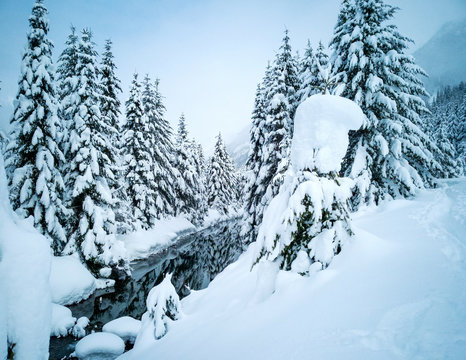 Snow covered frozen beautiful Gold Creek Pond with snow covered trees and trail during the winter in the Alpine Lakes Wilderness in Kittitas county Washington State