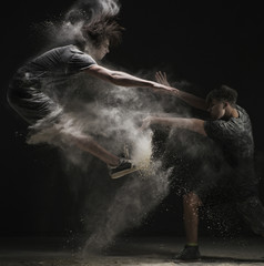 Two male dancers jumping in white dust cloud view