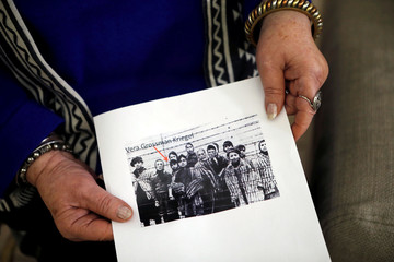 Holocaust survivor Vera Grossman Kriegel shows an image of herself as a child after the liberation of Auschwitz during an interview with Reuters in Oranit, in the Israeli-occupied West Bank