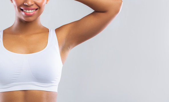 Cropped of african lady showing her clean armpit