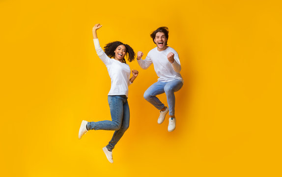 Cheerful girl and handsome guy jumping in air, having fun together