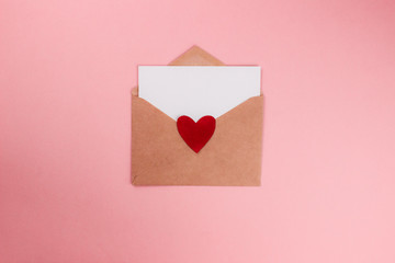 Love letter with white paper sheet in craft paper envelope with red heart flat lay on colorful pink background. 8 march, Mother's day, Valentine's Day template. Top view with copy space. Stock photo