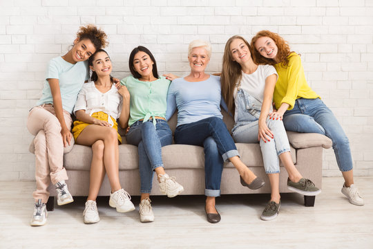 Women Of Different Age Sitting On Sofa Smiling Indoor