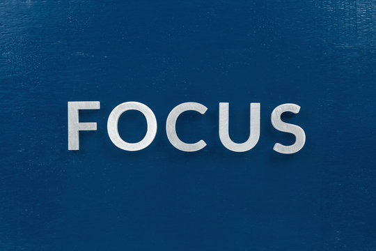 the word focus laid with silver metal characters on blue painted wooden board in flat lay with central composition
