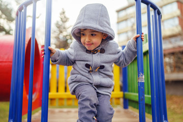 Portrait of small little caucasian boy kid wearing winter coat walking standing on the slide playground in the park with hood on his head in winter day smiling