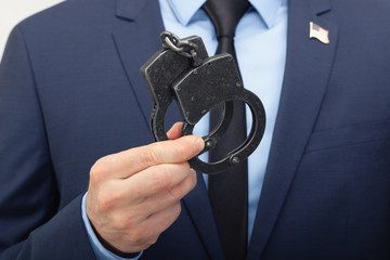 White man in suit holding handcuffs in hand with USA flag pin on his chest