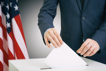 Caucasian male in suit holding ballot paper in hand and throwing it into election box with USA flag on background