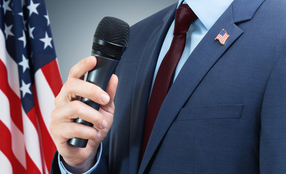 Man in suit holding microphone in hand with USA flag on background