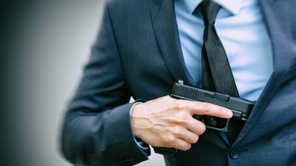 White man holding handgun in hand and covering it with his suit
