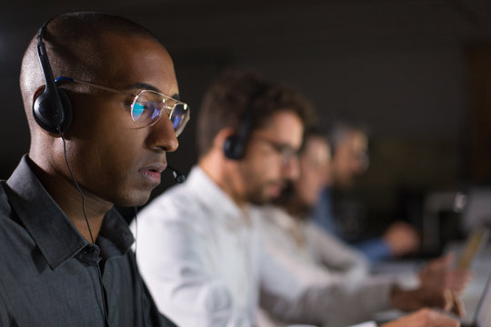 Concentrated call center operator communicating with client. African American young man in eyeglasses looking at laptop while serving client. Call center concept