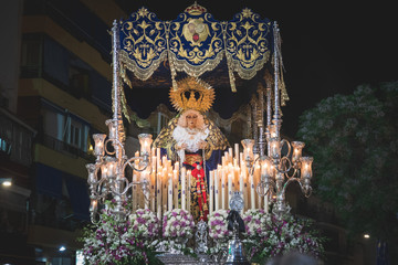 Virgen Maria in procession in Marbella at the holy week , candles an throne at night