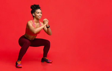 Happy black girl enjoying working out over red background Wall mural