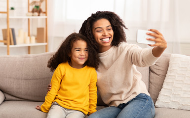 Happy Mother And Daughter Making Selfie Sitting On Sofa Indoor