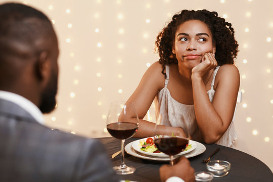 Bored afro woman attending first date at restaurant