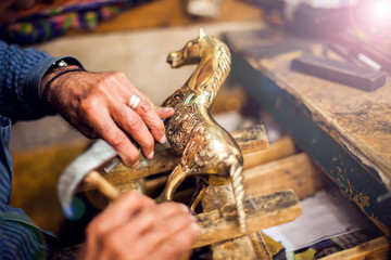 A man making embassed figure. Art and handwork industry