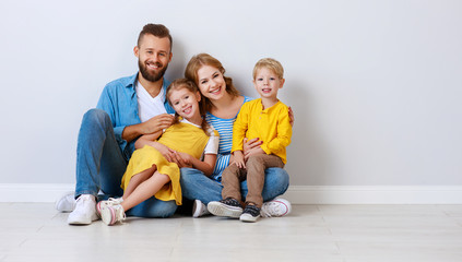 happy family mother father and children daughter and son  near an empty   blank wall