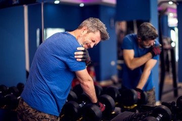 Man feeling strong shoulder pain while training with dumbbells in the gym. People, fitness and healthcare concept