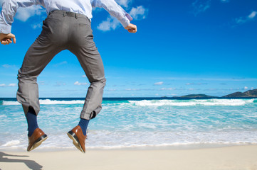 Unrecognizable businessman jumping into the air above a tropical beach clicking his heels together in celebration