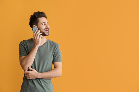 Happy young man talking by mobile phone on color background