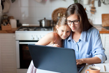 Mother and daughter using laptop and Internet. Freelancer workplace in cozy kitchen. Woman and child girl together. Concept of female business, working mom, freelance, home office. Lifestyle moment.