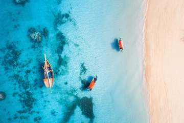 Door stickers Pool Aerial view of the fishing boats in clear blue water at sunset in summer. Top view from drone of boat, yacht, sandy beach in Zanzibar. Travel. Tropical seascape with sailboats, sea. View from above