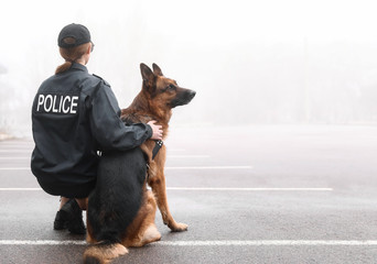 Female police officer with dog patrolling city street Fotomurales