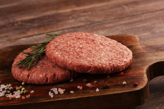 raw patty for angus burger on wooden cutting board. patty for burger