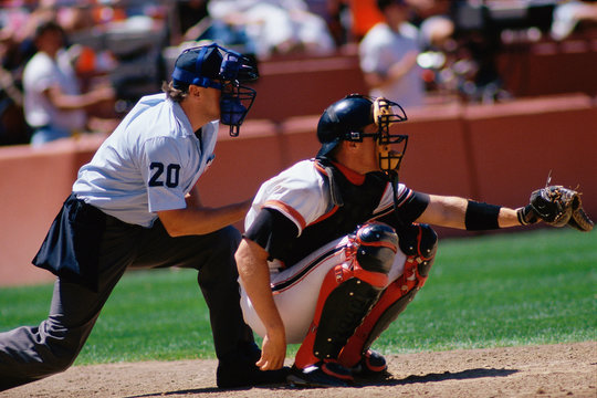 Baseball catcher and umpire at game