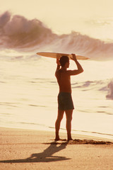 Young surfer carrying surfboard on his head