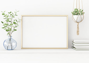 Interior poster mockup with horizontal gold metal frame on the table with plants in blue vase and hanging macrame pot on empty white wall background. A4, A3 size format. 3D rendering, illustration.