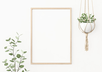 Interior poster mockup with vertical wooden frame on empty white wall decorated with plant branch and hanging macrame pot. A4, A3 size format. 3D rendering, illustration.