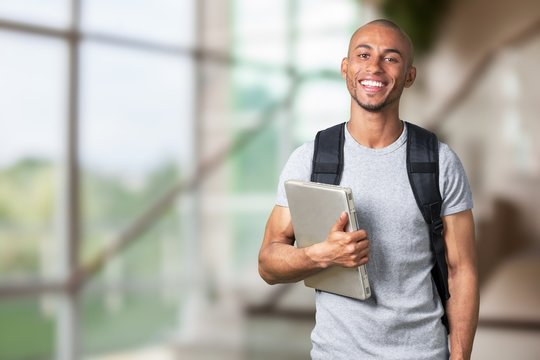 Smiling young black college student with laptop