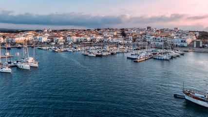 Widescreen aerial view of lagoon with moored boats and yachts. Blue color of sea. Drone photo. Beauty cloudy sunset on Sardinia, Mediterranean island. Vacation and tourism concept.