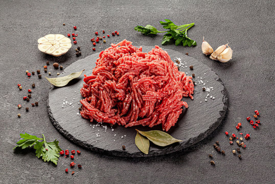 Raw meat products. Veal or mixed homemade minced meat with spices on a black background. board background image, copy space text