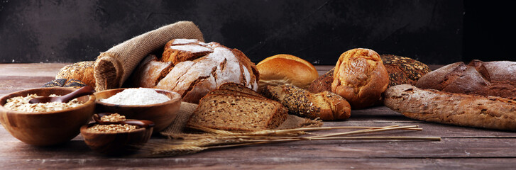 Tuinposter Brood Assortment of baked bread and bread rolls and cutted bread on table background