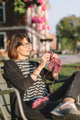 Close up photo of pleased attractive woman in glasses, black jeans and striped t-shirt. Charming female knitting something from pink yarn. Outdoor recreation. Needlework and hobby concept.