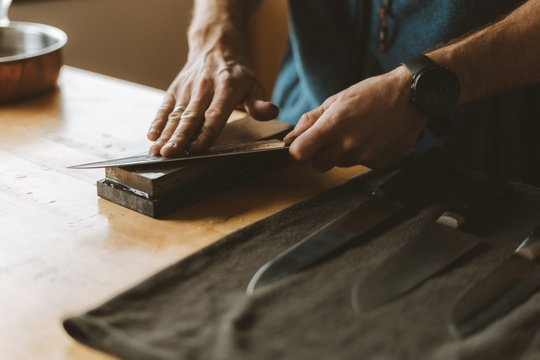 Person sharpening knives with a whetstone in the kitchen