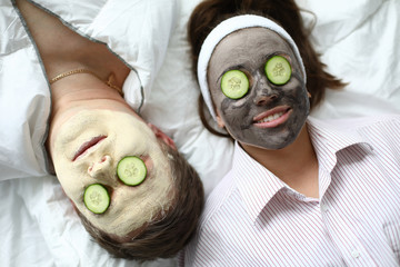 Foto auf Gartenposter Spa Top-view of man and woman making spa procedures applying wetting facial masks and fresh cucumber on eyes. Couple laying on bed. Wellness and skincare concept
