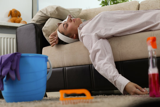 Portrait of tired woman laying on couch surrounded by cleaning supplies. Exhausted housewife brushed hairy carpet with detergent spray. Housekeeping and clean-up concept