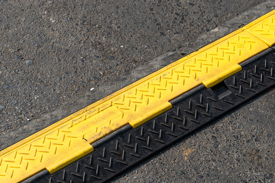 Close up of yellow and black color of speed bump or obstacle on the asphalt road to reduce vehicle speed.