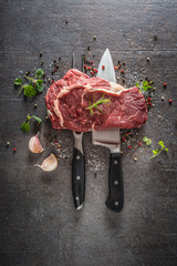 Raw beef steak with fork and knife salt pepper and herbs on dark concrete background
