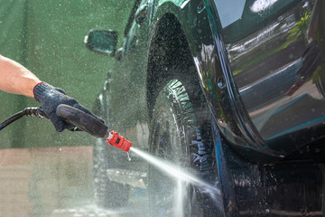 People cleaning car with high pressure water