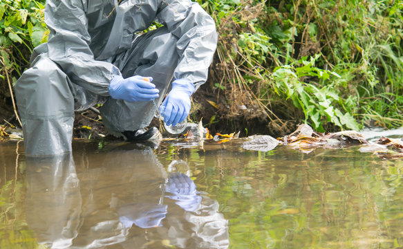 a scientist in a protective suit and blue gloves, conducts research on the ground, holds a glass flask in his hand and takes a sample of water from the river